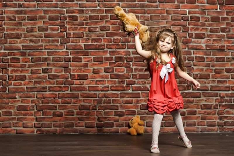 Girl throwing teddy bear