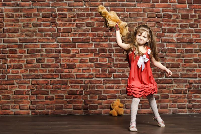 Girl throwing teddy bear